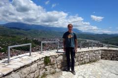 Stefan på Berat Castle viewpoint med delar av Berat och Mount Tomorr i bakgrunden.