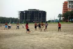 Fotboll på stranden i Cox's Bazar framför ett av många ej färdigställda och övergivna hotell.