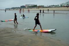 Grabbarna leker med surfingbrädor på stranden i Cox's Bazar.