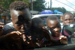 Gatubarn som sprungit fram till taxin vid ett trafikljus för att tigga pengar, Dar es-Salaam.