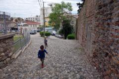 Två lokala grabbar springer uppför kullerstensgatan vid amfiteatern, Durrës.
