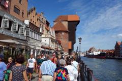 Packat med folk längs gågatan Długie Pobrzeże. På bilden syns en del av Żuraw (den medeltida hamnkranen) som byggdes i mitten på 1400-talet. Den totalförstördes 1945 och återuppbyggdes 1957-1969.