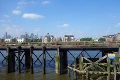 Gammal konstruktion i Themsen med Docklands i bakgrunden.