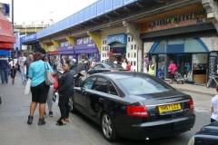 På bortre sidan av gatan en av entréerna till Brixton Village, Brixton.