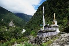 Stupa och tibetanskt mantra längs leden mellan Lukla och Phakding.