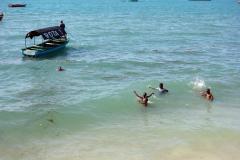 Barnen verkar älska att bada på denna ö. Den publika stranden i Stone Town (Zanzibar Town), Unguja.