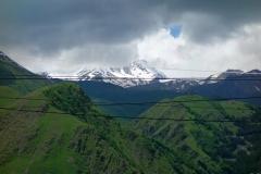 Gergeti Trinity-kyrkan på 2170 meters höjd med Kaukasus-bergen från Stepantsminda.