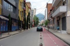 Gatuscen i vackra Tirana med berg i bakgrunden.