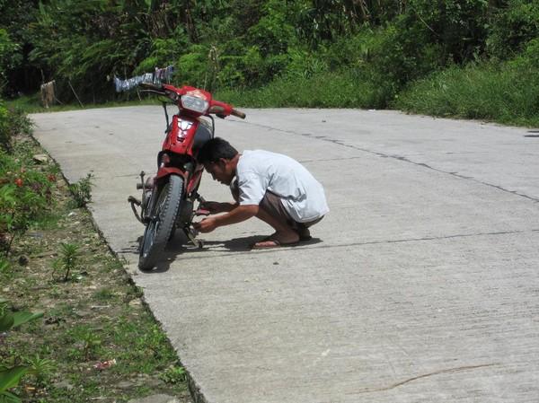 Min chaufför fixar motorcykeln. Som vanligt är det något som strular. Denna motorcykel var väldigt gammal. I närheten av Lake Danao.