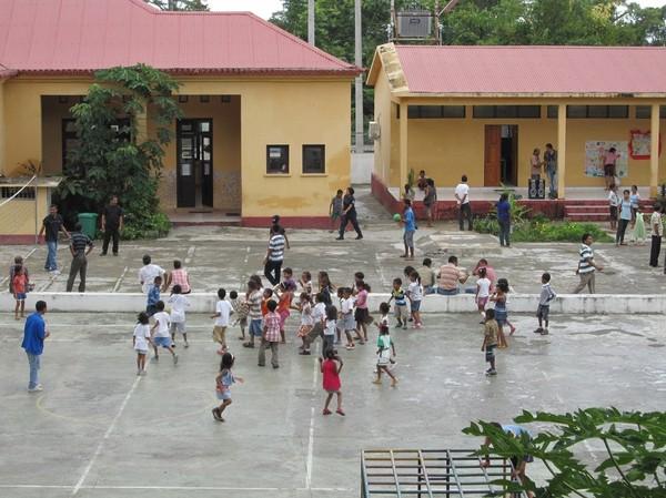 Skolgården nedanför Restaurante Amalia med fotbollsmatch för barnen, Baucau old town, Timor-Leste.