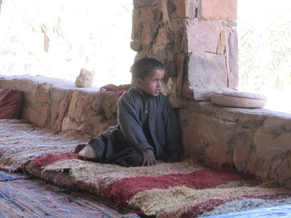 Beduin pojke inspekterar sandstormen utanför huset.