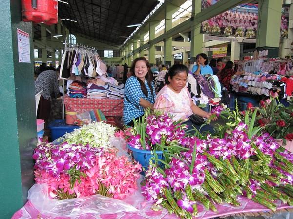 Försäljerskor av blommor och kläder, marknaden i Roi et.