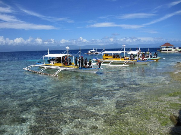 Dykbåtar på väg ut mot nya äventyr tidigt på morgonen, Panagsama beach, Moalboal.