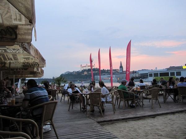 Party crowd vid konstgjorda beachen längs Donau med Bratislava castle i bakgrunden, Petrzalka, Bratislava.