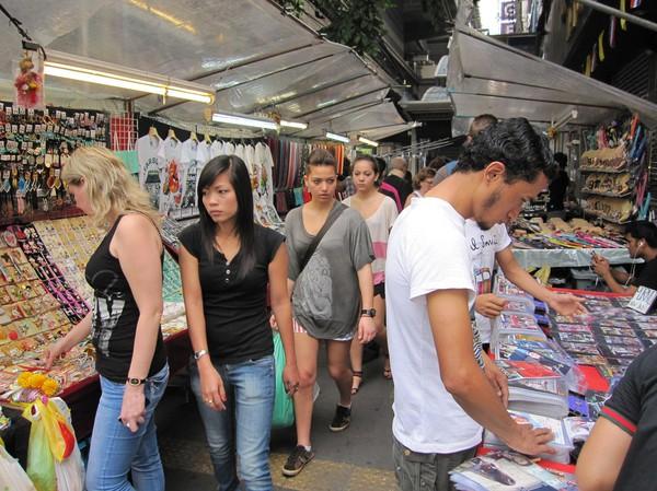 Internationella besökare av marknadsstånden längs Sukhumvit road, Bangkok.