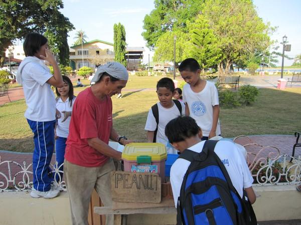 Min vän Jose med skolbarn som vill köpa peanuts av honom. Han berättade för mig om Marcostiden och mycket annat, Cateel.