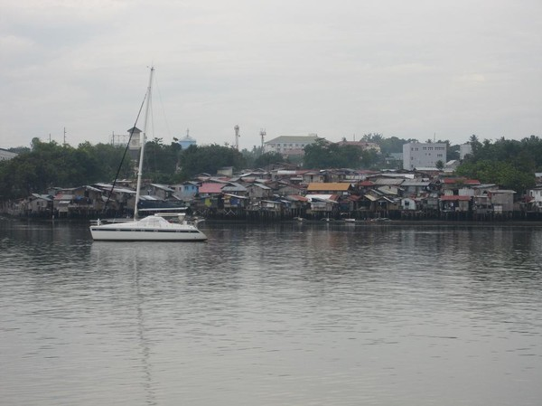 Kontraster med lyxbåt i förgrunden och squatter-bostäder i bakgrunden på Mactan island. Båtresan mellan Ormoc city och Cebu city.