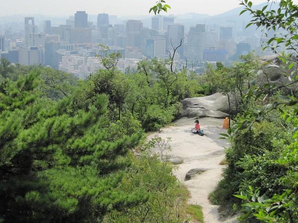Bra bild, med en kvinna som ber och Seoul i bakgrunden.