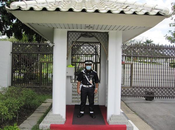 Den ena av två väktare vid entrén till Istana Nurul Iman.