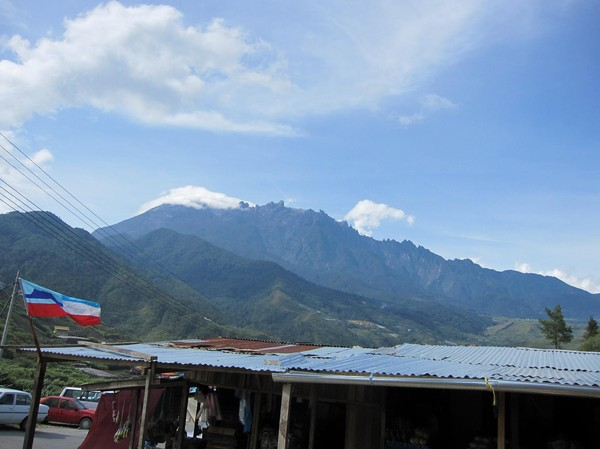 Mount Kinabalu sedd från den lilla byn Kandasan. Till vänster i bild syns Sabah's flagga.