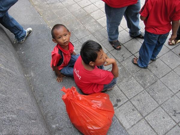 Barn som väntar på att pappa och mamma ska bli färdiga med sin gatushopping.