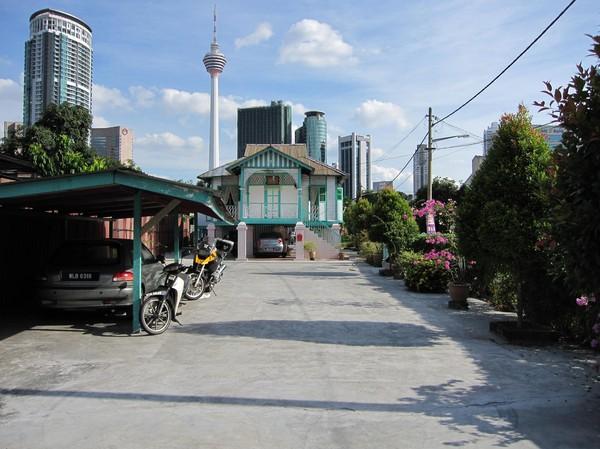Gammalt, vackert bostadshus i trä i stadsdelen Kampung Baru. Menara KL Tower i bakgrunden.