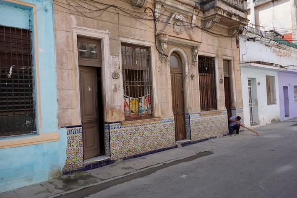 Fin fasad med man till höger i bild som jobbar på ett trästycke av något slag. Centro Habana, Havanna.