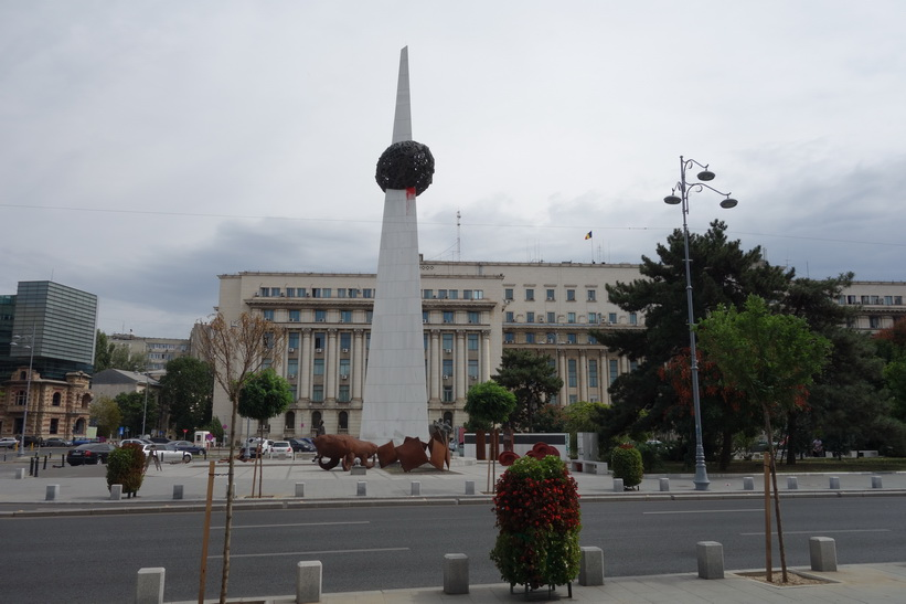 Piata Revoluției med kommunisthögkvarteret i bakgrunden, Bukarest. Det vita pelaren är ett minnesmonument för revolutionens offer.