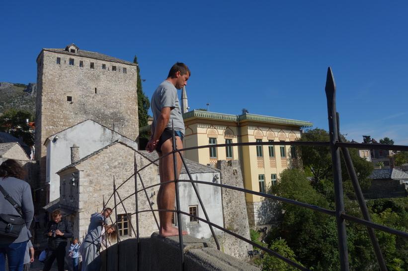 Från toppen av Stari Most (21 meter över vattenytan) förbereder sig denna man på att hoppa. Hopp utförs när tillräckligt med stålar samlats in från publiken, Mostar.