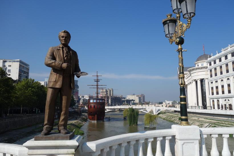 En av många statyer på Skopje Art Bridge. Skopje Eye Bridge i bakgrunden.