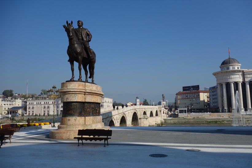 Monument i centrala Skopje. The Stone Bridge i bakgrunden.
