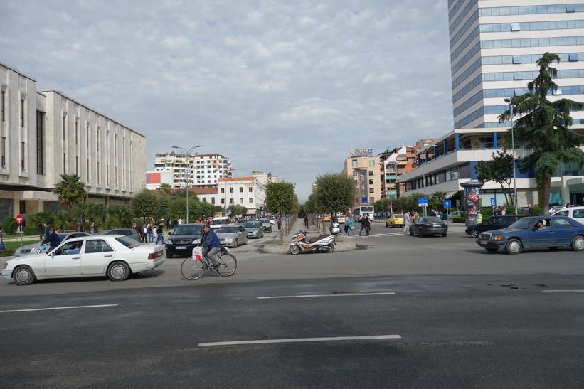 Gatuscen i centrala Tirana med del av Tirana International Hotel till höger i bild.
