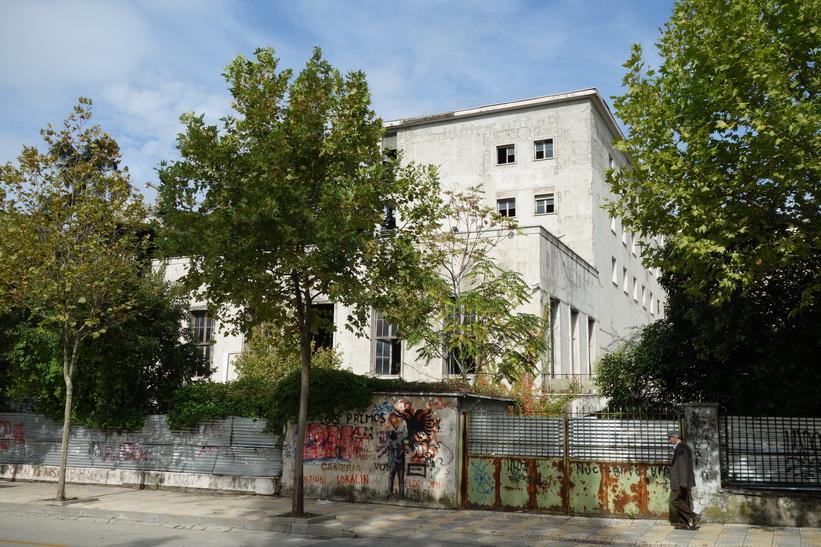 Klotter längs en avspärrning till en gammal kommunistbyggnad i centrala Tirana.