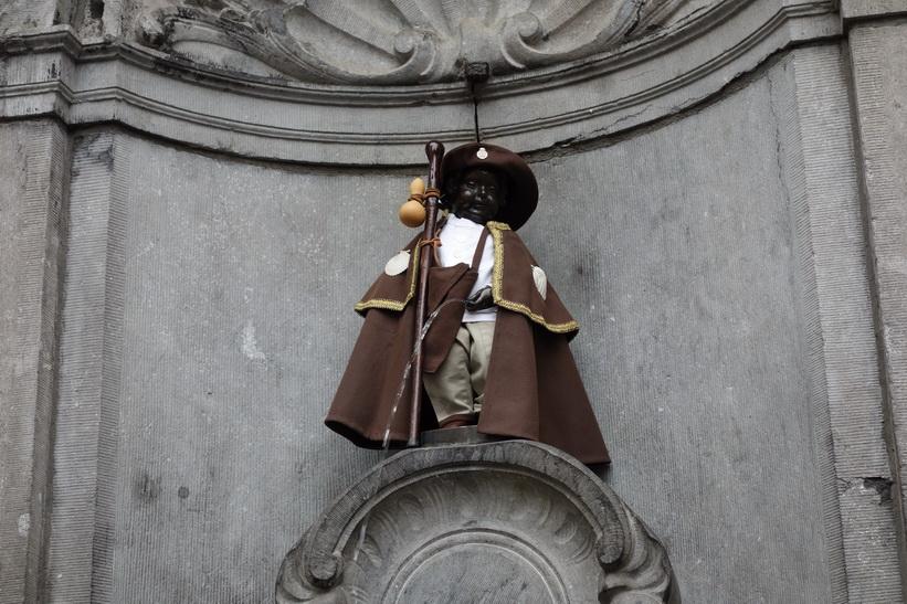 Manneken Pis, det kända landmärket i Bryssel. En liten bronsfontänskulptur föreställande en naken pojke som urinerar i fontänens bassäng. För att skyla den nakna pojken så klär man på honom. Kläderna byts ofta.