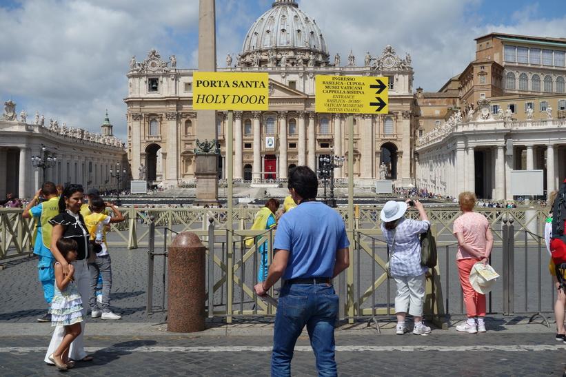 Skylt på Petersplatsen som visar vilken riktning man ska ta för att hitta till Peterskyrkans entré, Vatikanstaten, Rom.