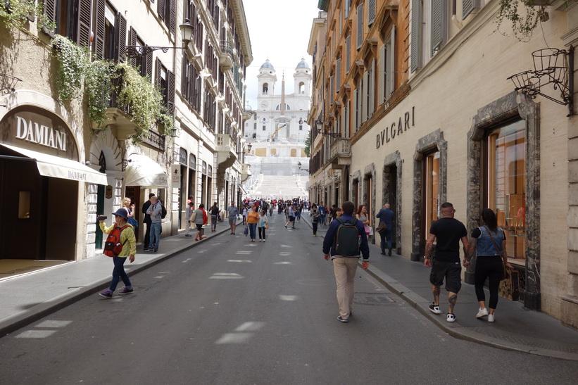 Gatan Via dei Condotti med spanska trappan och kyrkan Trinità dei Monti i bakgrunden, Rom.