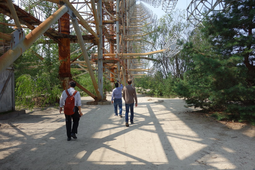 En japan, en iranier och en norrman promenerar under The Russian Woodpecker.