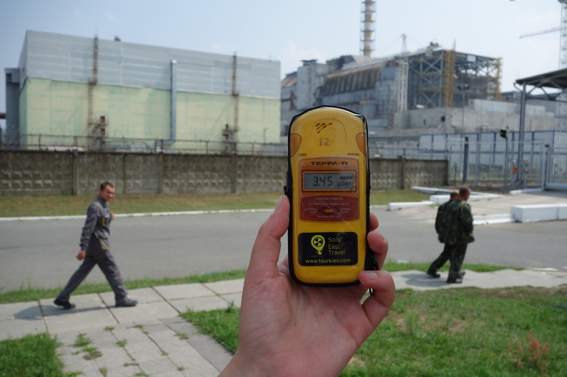 Här mäter jag upp 3.45 mikrosievert när jag riktar geigermätaren mot reaktor 4. I bakgrunden ses några av de arbetare som jobbar med den nya sarkofagen passera förbi, Tjernobyl.