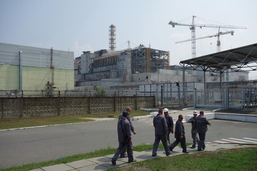 Arbetare som jobbar med den nya sarkofagen framför reaktor 4. 250 000 ton betong består den gamla sarkofagen av, Tjernobyl.