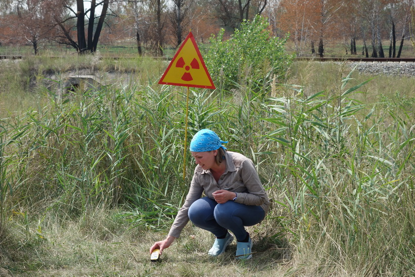 Daria mäter strålningen vid en av skyltarna som varnar för strålning. Runt 20 mikrosievert uppmättes på denna plats som också låg vid Pripyats stadsskylt.