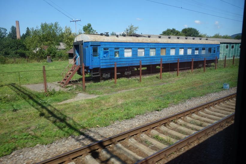 En tågstation med en gammal tågvagn som är tagen ur bruk. Tågresan mellan Lviv och Uzhhorod.