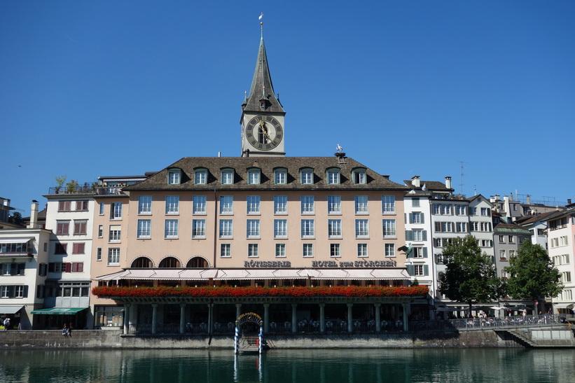 Färjeläger Zürich Storchen vid floden Limmat med klocktornet på St. Peterskirche i bakgrunden, Zürich.