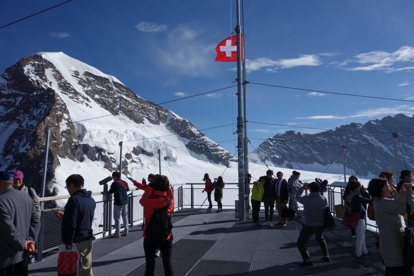Massor med asiatiska turister på Sphinx-terrassen med Mönch i bakgrunden, Jungfraujoch.