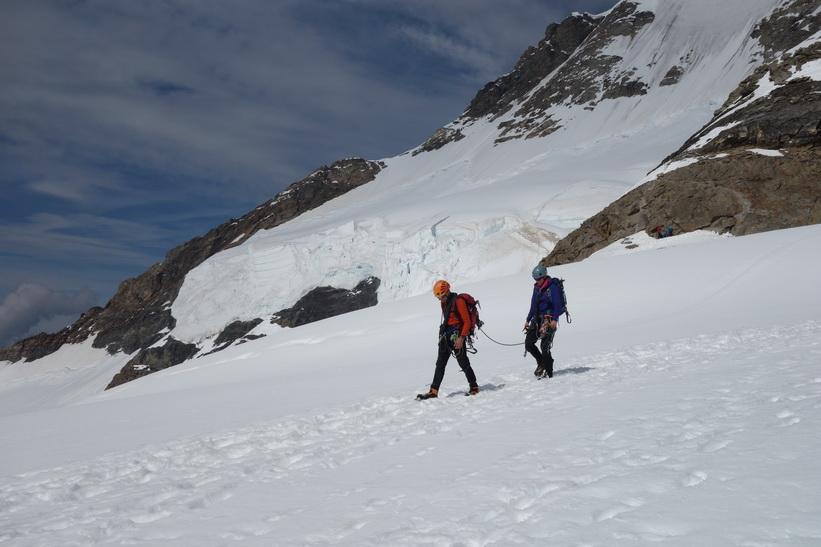 Två personer närmar sig. Vy under promenaden från Mönchsjochhütte tillbaka ner till Jungfraujoch.