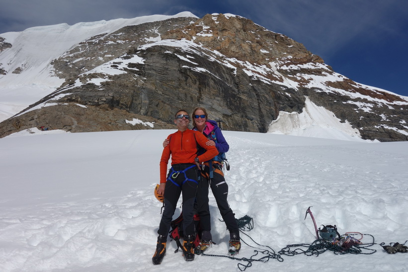 Schweiziskt överlyckligt par som precis har bestigit Mönch för första gången. Promenaden från Mönchsjochhütte tillbaka ner till Jungfraujoch.