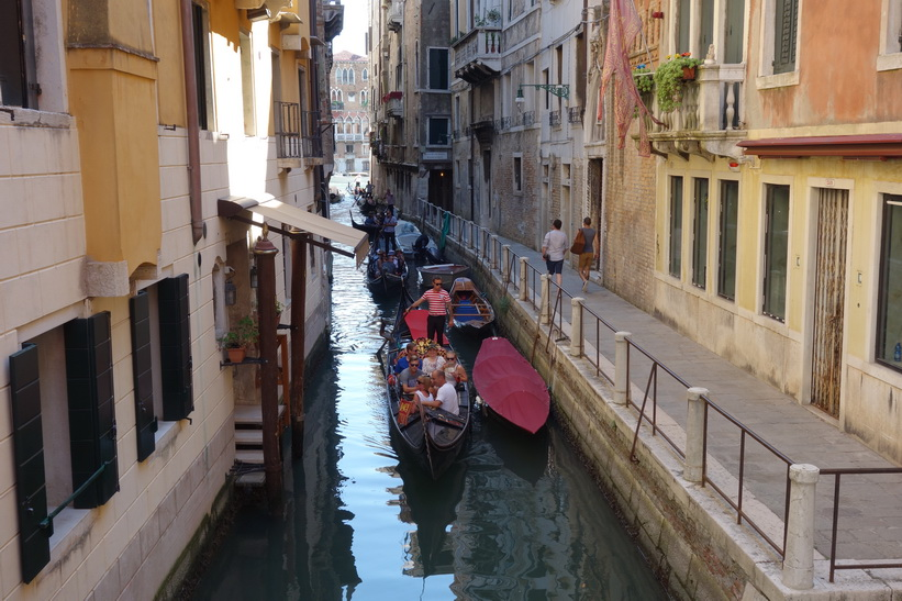 Kanal med turister i gondoler, Venedig.