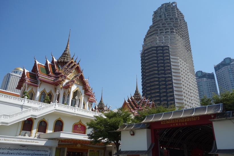 Wat Yannawa med övergivna skyskrapan Sathorn Unique Tower i bakgrunden, Bangkok.